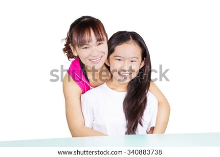 Mother and young daughter sitting front of desk