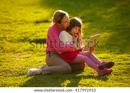 mother and young daughter sitting in Park on green grass.