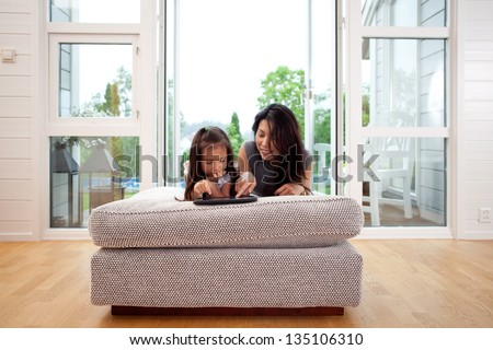 Mother and young daughter using a digital tablet in a living room interior - stock photo