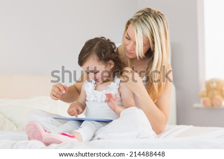 Mother and young daughter using digital tablet on bed at home