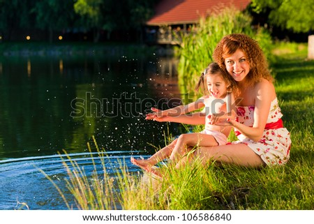 mother and young douther at the lake enjoying a sunset - stock photo