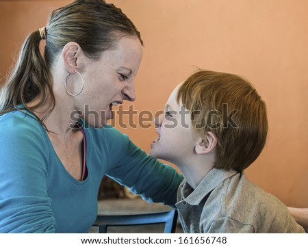 Mother and young son playfully snarling at each other - stock photo
