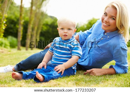 Mother And Young Son Sitting In Garden Together