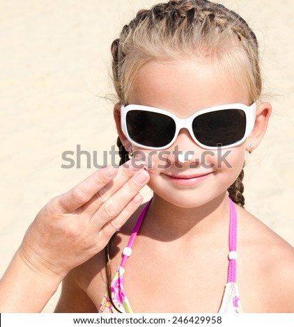 Mother anoints protective cream to face  little girl on the beach - stock photo