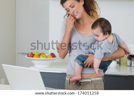 Mother answering cellphone while carrying baby boy in kitchen - stock photo