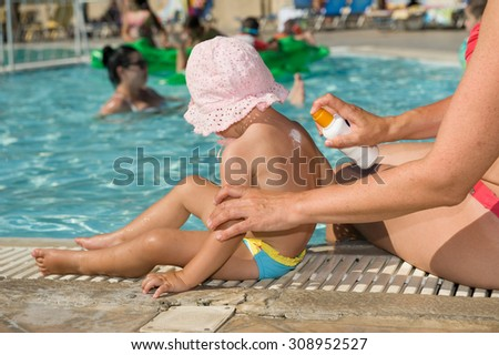 Mother applying Baby suncream on the pool in summer