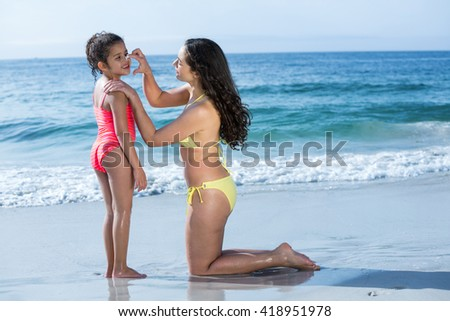 Mother applying cream to happy daughter at sea shore - stock photo