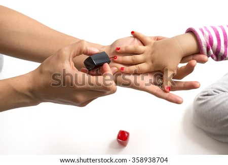 mother applying nail polish to her little girl - stock photo