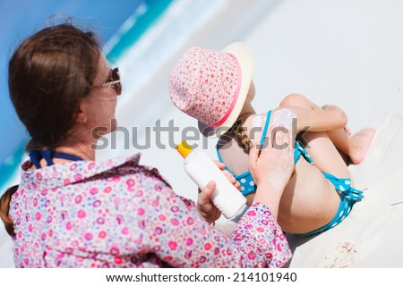 Mother applying sunblock cream on her daughters shoulder - stock photo