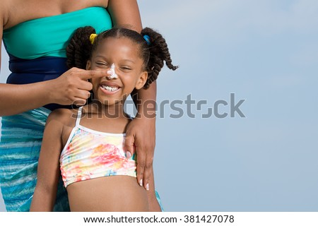 Mother applying suncream to daughters nose - stock photo