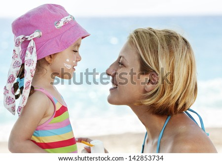 Mother applying suntain lotion to her child on the beach, protecting from the sun