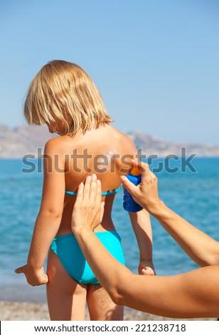 Mother applys sunblock cream on daughter's back - stock photo