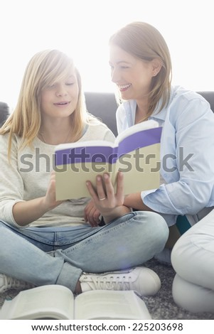 Mother assisting daughter in homework at home - stock photo