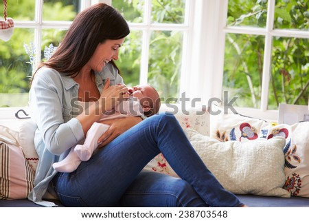 Mother At Home Cuddling Newborn Baby At Home - stock photo