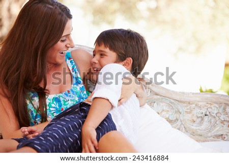 Mother At Home Sitting On Outdoor Seat And Playing With Son - stock photo