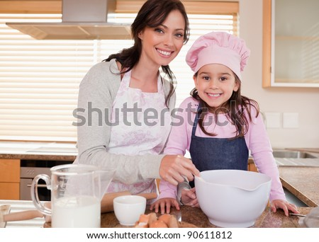 Mother baking with her daughter in a kitchen - stock photo