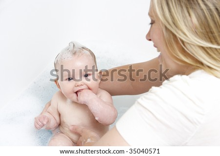 Mother Bathing Baby At Home