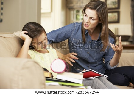 Mother Becoming Frustrated With Daughter Whilst Doing Homework Sitting On Sofa At Home - stock photo