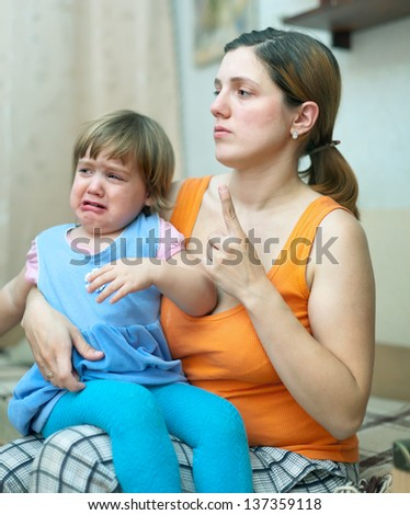 Mother berates  crying child in interior - stock photo