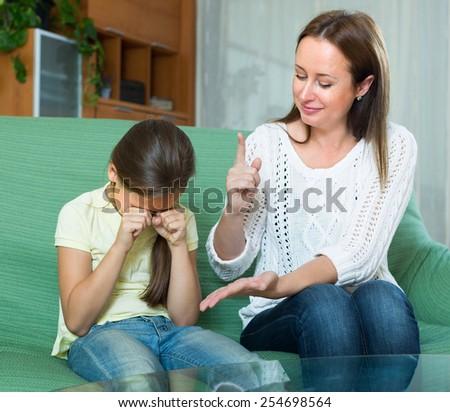 Mother berating  crying daughter at interior - stock photo
