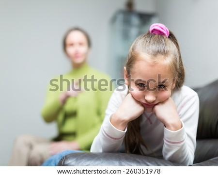 Mother berating  daughter at interior - stock photo