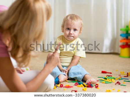 Mother berating her little kid son for disorder at home - stock photo