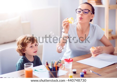 Mother blowing bubbles with son - stock photo
