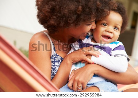 Mother bonding with young son sitting in a hammock - stock photo