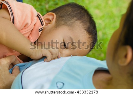 Mother breast feeding her baby boy in a park.