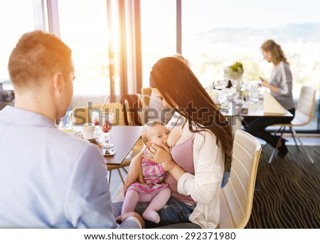 Mother breast feeding her little daughter in a cafe - stock photo