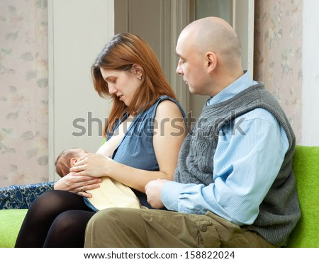 Mother breast feeding newborn baby at home. Father looks at the child  - stock photo