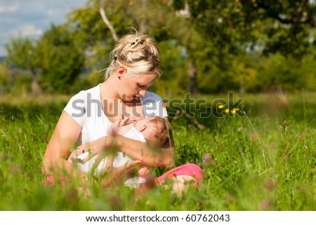 Mother breastfeeding her baby on a great sunny day in a meadow with lots of green grass and wild flowers - stock photo