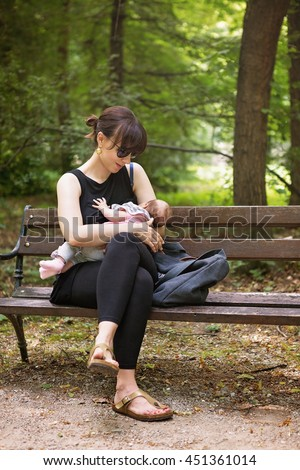 Mother breastfeeding her newborn baby girl in the park, sitting on the bench under the trees, instagram style effect applied
