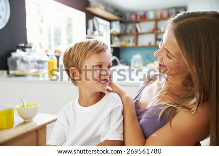 Mother Brushes Son's Hair As He Plays With Digital Tablet - stock photo