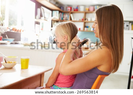 Mother Brushing Daughter's Hair At Breakfast Table - stock photo