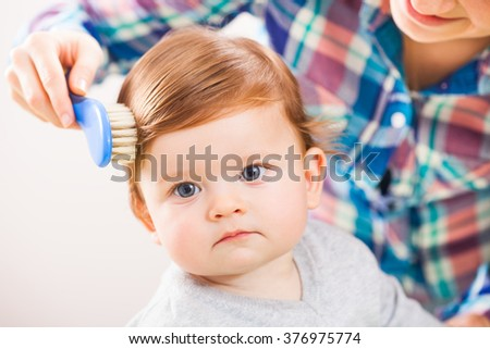 Mother brushing hair of her baby boy - stock photo