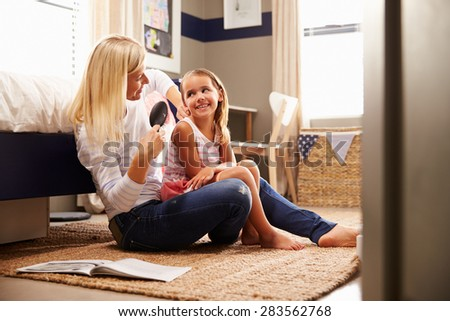 Mother brushing young daughter's hair - stock photo