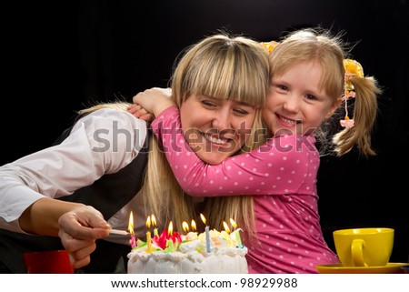 Mother burning candles in her birthday with her happy daughter - stock photo
