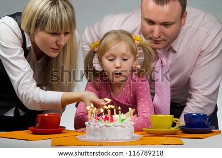 Mother burning candles in her birthday with her happy family - stock photo