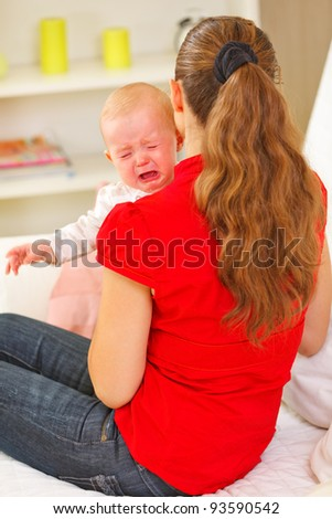 Mother calming crying baby - stock photo