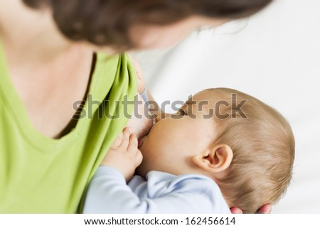 Mother care concept: Mother breast feeding her baby. - stock photo