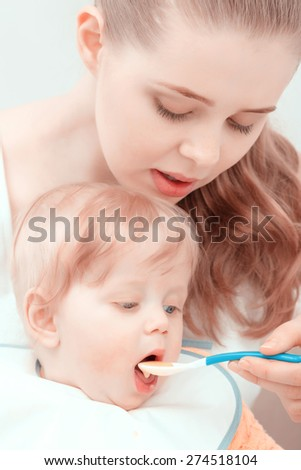 Mother care. Happy young mother feeding her baby with a spoon  - stock photo