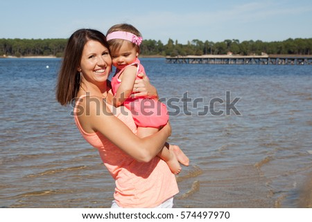 mother carries her little girl during holiday on the beach