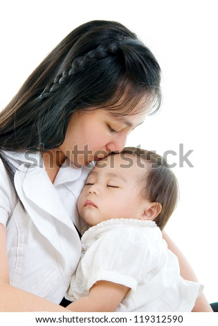 mother carrying and kissing her sleeping baby - stock photo