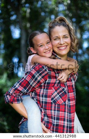 Mother carrying daughter on back while standing in back yard - stock photo