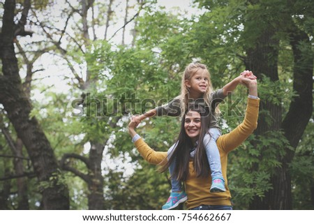Mother carrying daughter on shoulders.