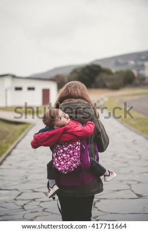 Mother carrying her child in a promenade in a backpack outdoors in a cloudy day