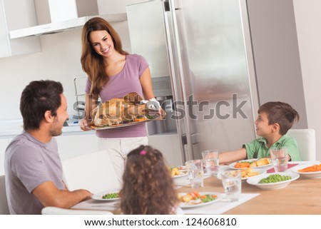 Mother carrying roast turkey for dinner in kitchen - stock photo