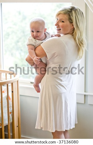 Mother carrying seven month old baby beside crib - stock photo