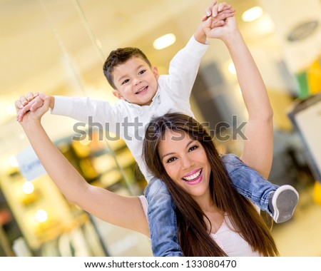 Mother carrying son on her shoulders at the shopping center - stock photo